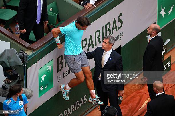 Rafael Nadal of Spain climbs down on to the court after celebrating in his player's box with his family and team following his victory in his men's...
