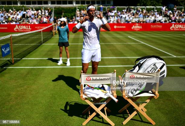 Rafael Nadal of Spain drinks water at his seat as he plays against Lucas Pouille of France during the Aspall Tennis Classic at Hurlingham on June 29...