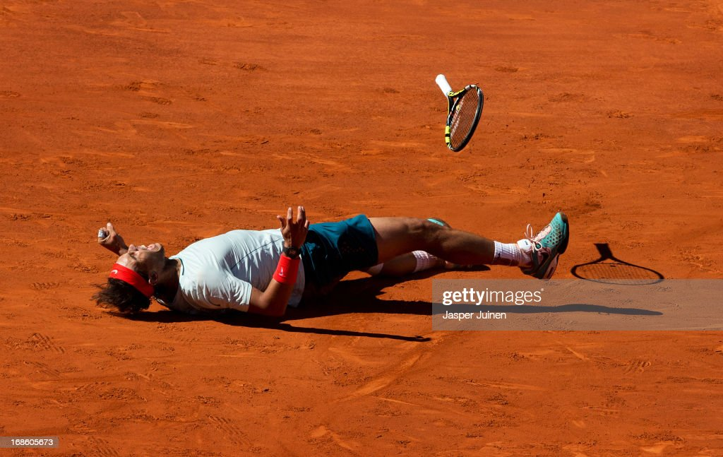 Rafael Nadal of Spain falls on his back celebrating matchpoint over Stanislas Wawrinka of Switzerland after winning the final match on day nine of the Mutua Madrid Open tennis tournament at the Caja Magica on May 12, 2013 in Madrid, Spain.
