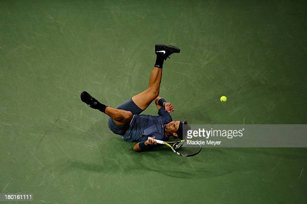Rafael Nadal of Spain falls over during his men's singles final match against Novak Djokovic of Serbia on Day Fifteen of the 2013 US Open at the USTA...