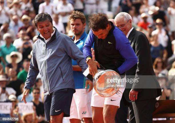 Rafael Nadal of Spain grabs the trophy after victory as coach Toni Nadal looks on during the men's singles final against Stan Wawrinka of Switzerland...