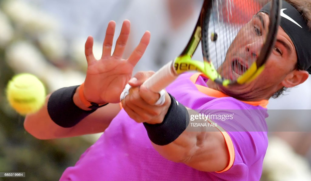 TOPSHOT - Rafael Nadal of Spain hits a return to Dominic Thiem of Austria during their quarter-final tennis match at the ATP Tennis Open tournament on May 19, 2017 at the Foro Italico in Rome. Austria's Dominic Thiem sent Rafael Nadal crashing out of the Rome Masters with a 6-4, 6-3 quarter-final victory, ending the Spaniard's 17-match winning run. /