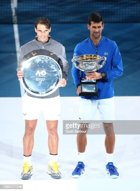 Rafael Nadal of Spain holding the runnersup trophy and Novak Djokovic of Serbia holding the Norman Brookes Challenge Cup pose for a photo following...