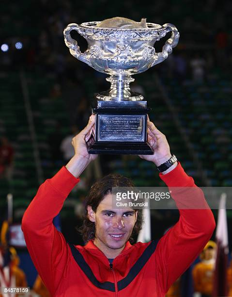 Rafael Nadal of Spain holds aloft the Norman Brookes Challenge Cup after winning his men's final match against Roger Federer of Switzerland during...