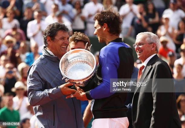 Rafael Nadal of Spain holds the trophy after victory with coach Toni Nadal looks on during the men's singles final against Stan Wawrinka of...