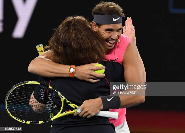 Rafael Nadal of Spain hugs local firefighter Deb Borg as he and the world's top players play in the Rally for Relief charity tennis match in support...