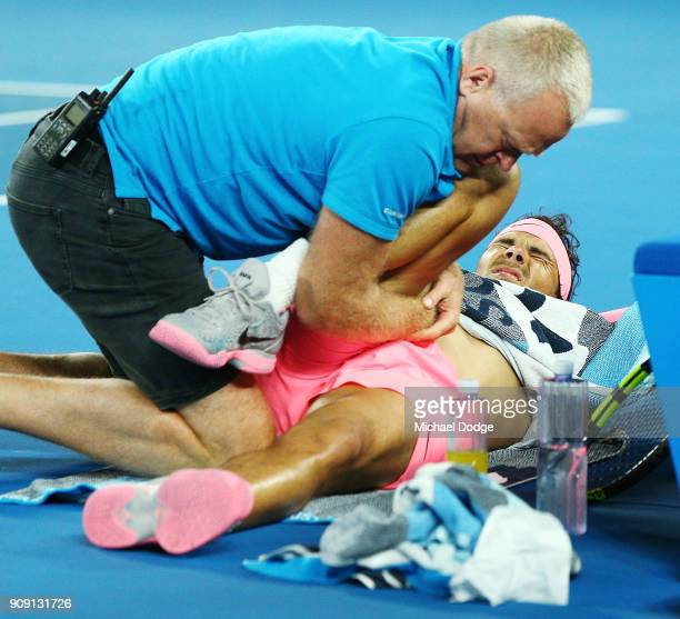 Rafael Nadal of Spain is attended to by a trainer as he has injury time out in his quarterfinal match against Marin Cilic of Croatia on day nine of...