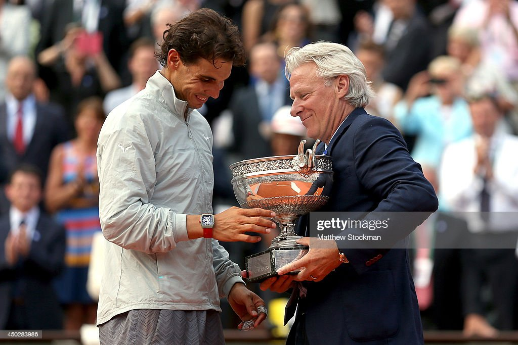 Rafael Nadal of Spain is presented with the Coupe de Mousquetaires by Bjorn Borg after his men's singles final match against Novak Djokovic of Serbia on day fifteen of the French Open at Roland Garros on June 8, 2014 in Paris, France.