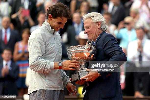 Rafael Nadal of Spain is presented with the Coupe de Mousquetaires by Bjorn Borg after his men's singles final match against Novak Djokovic of Serbia...