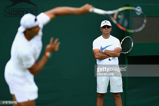 Rafael Nadal of Spain is watched by his coach Toni Nadal during a practice session prior to the Wimbledon Lawn Tennis Championships at the All...