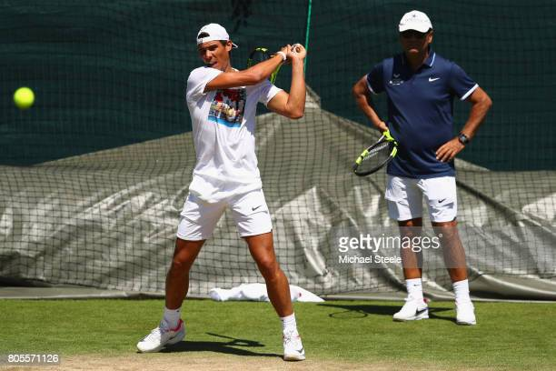 Rafael Nadal of Spain is watched closely by coach Toni Nadal during a practise session at Wimbledon on July 2 2017 in London England