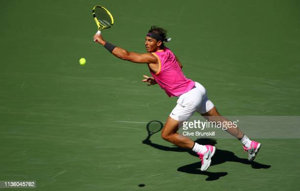 Rafael Nadal of Spain leaps to play a backhand against Karen Khachanov of Russia during their men's singles quarter final match on day twelve of the...