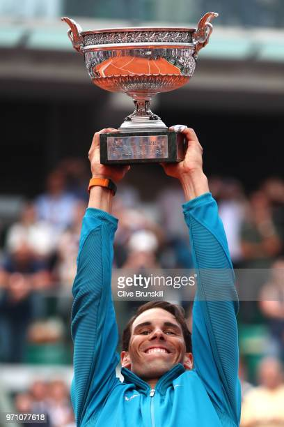 Rafael Nadal of Spain lifts the Musketeers' Cup as he celebrates victory following the mens singles final against Dominic Thiem of Austria during day...