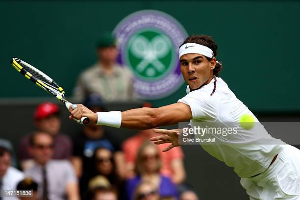 Rafael Nadal of Spain lines up a shot during his Gentlemen's Singles first round match against Thomaz Bellucci of Brazil on day two of the Wimbledon...