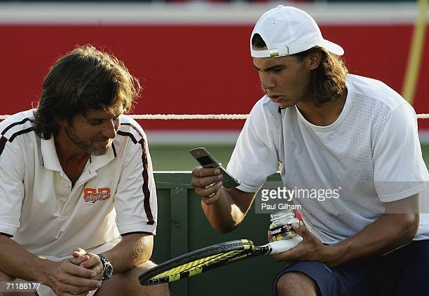 Rafael Nadal of Spain looks at his mobile phone as he talks to Francisco Roig on a practice court during the Stella Artois Championships at Queens...