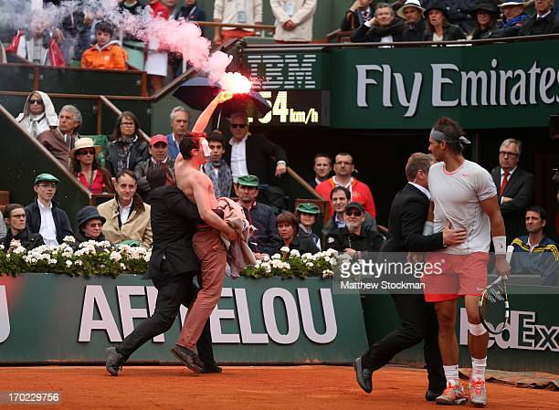 Rafael Nadal of Spain looks on as security guards restrain a protester after he lit a flare and ran on court before the start of a game in the Men's...