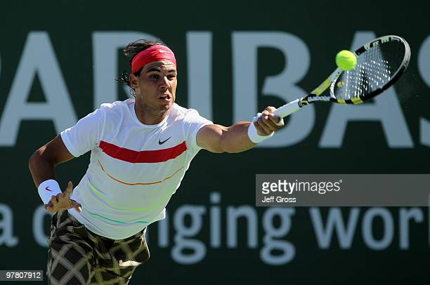 Rafael Nadal of Spain lunges to return a forehand to John Isner of the USA during the BNP Paribas Open at the Indian Wells Tennis Garden on March 17...