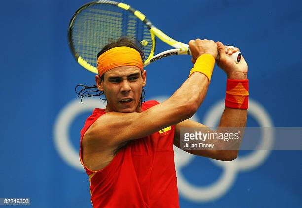 Rafael Nadal of Spain plays a backhand to Potito Starace of Italy during the Men's Singles First Round at the Olympic Green Tennis Center on Day 3 of...
