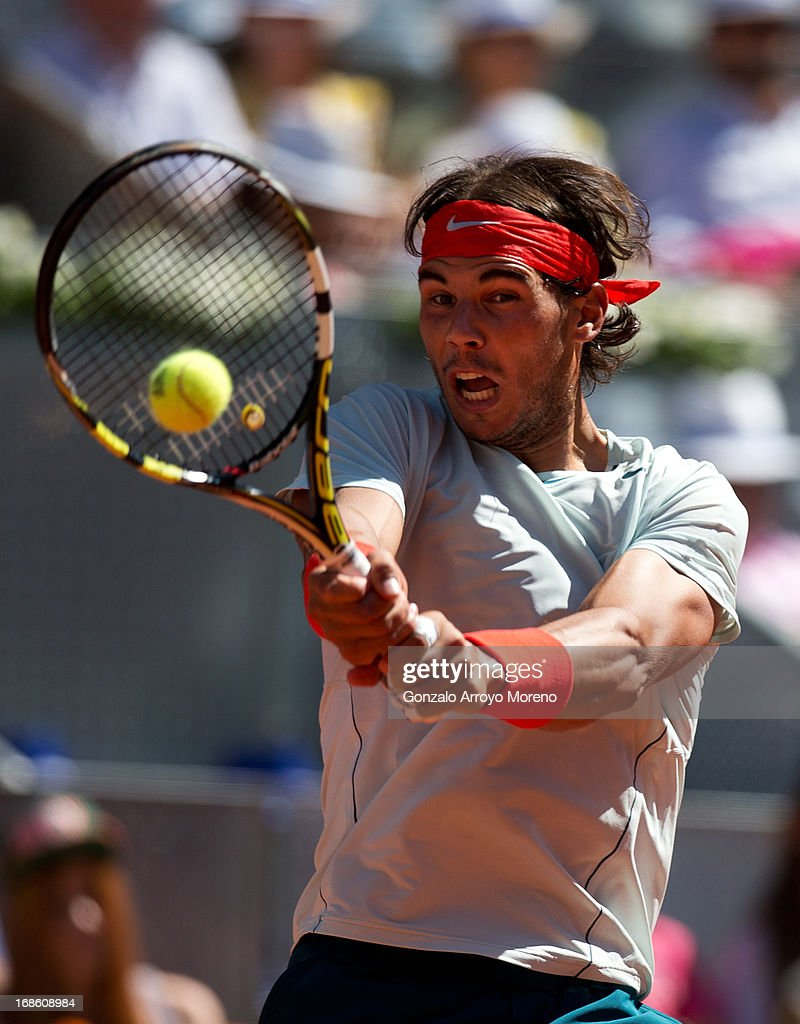 Rafael Nadal of Spain plays a doublehanded backhand to Stanislas Wawrinka of Switzerland during the final match on day nine of the Mutua Madrid Open tennis tournament at the Caja Magica on May 12, 2013 in Madrid, Spain.