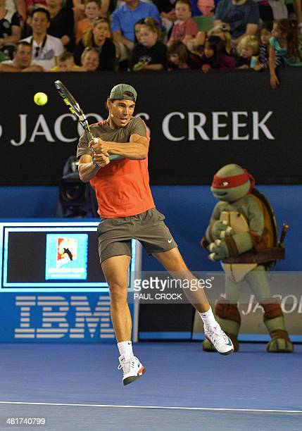 Rafael Nadal of Spain plays a shot in front of cartoon character 'Rafael' the Teenage Mutant Ninja Turtle during the Kids Day exhibition match ahead...