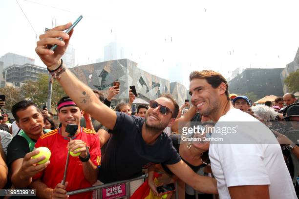 Rafael Nadal of Spain poses for a selfie with a fan during a Kia Key handover ceremony at Federation Square ahead of the 2020 Australian Open at...