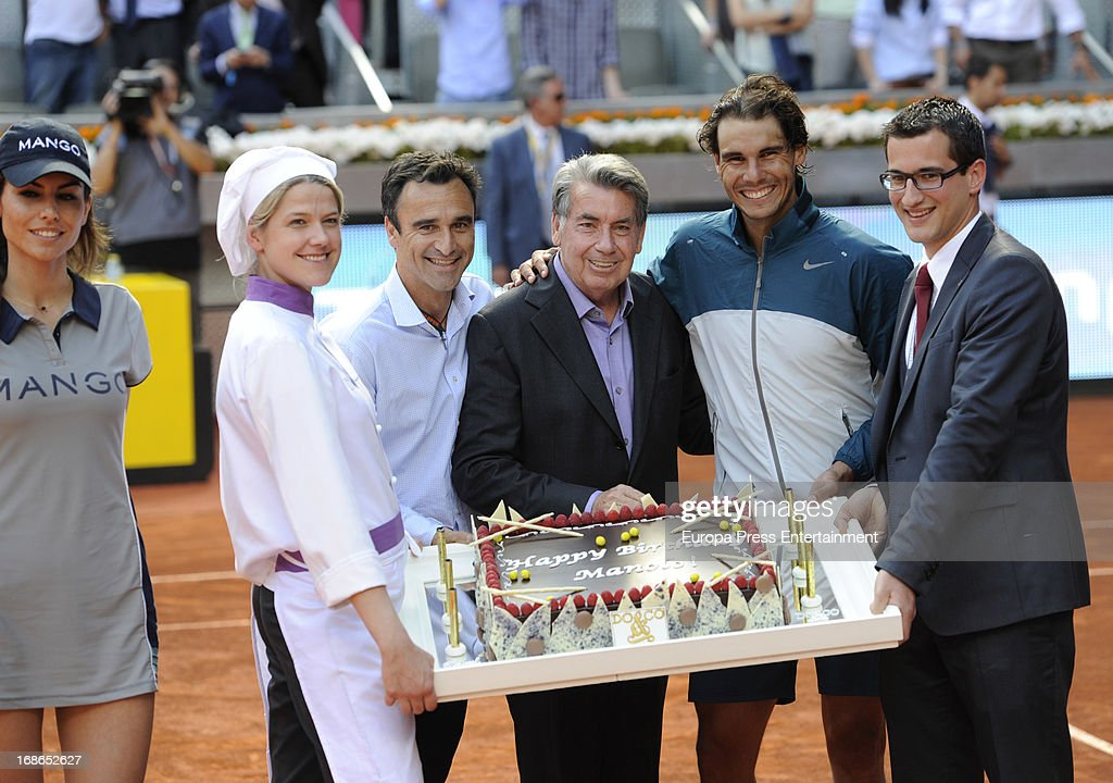 Rafael Nadal (2R) of Spain poses with former tennis player Manolo Santana (C) who is presented with a Birthday cake during the Mutua Madrid Open tennis tournament at La Caja Magica on May 12, 2013 in Madrid, Spain.