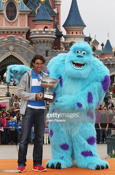 Rafael Nadal of Spain poses with 'Sulley' and the Coupe des Mousquetaires trophy as he celebrates his eighth French Open title at Disneyland Resort...