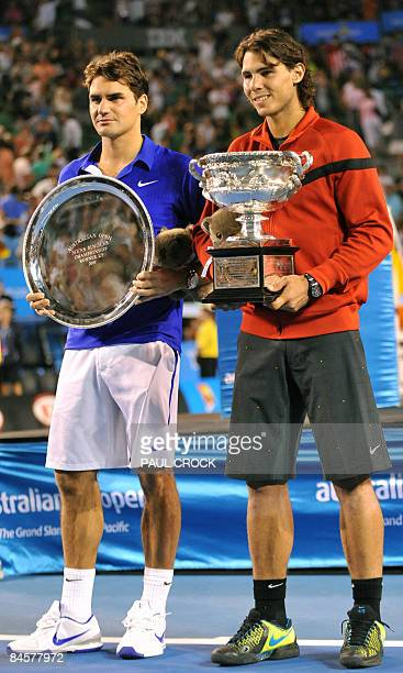 Rafael Nadal of Spain poses with the winner's trophy alongside Roger Federer of Switzerland after victory in their men's singles match at the...