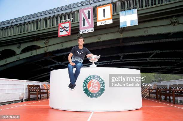 Rafael Nadal of Spain poses with the winner's trophy during a photocall to celebrate his record breaking 10th French Open title on the Seine River on...