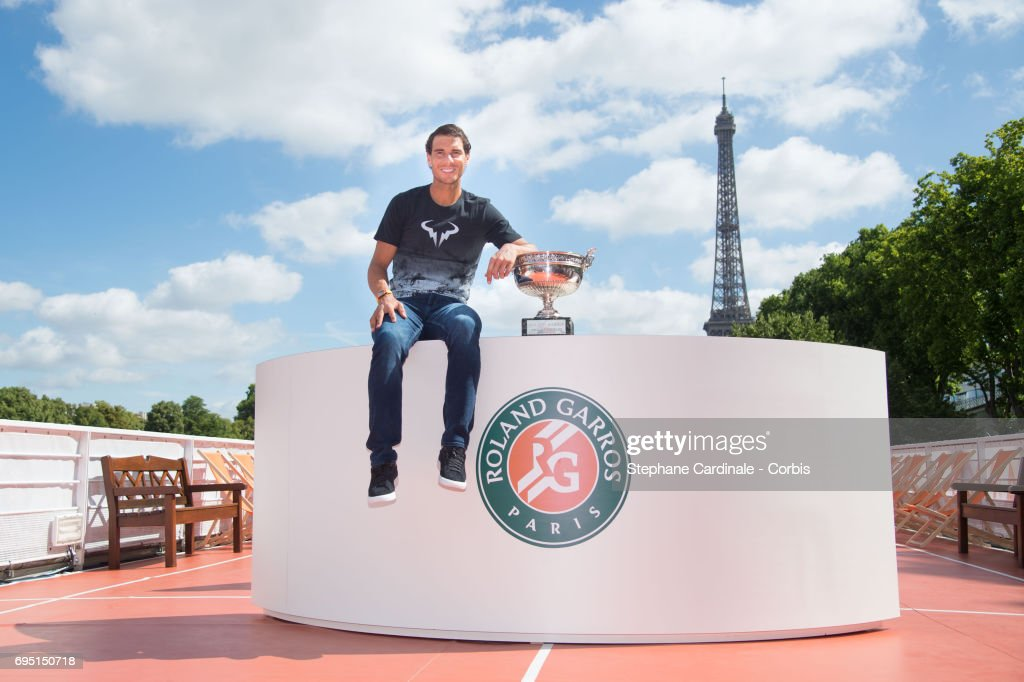 Rafael Nadal of Spain poses with the winner's trophy next to the Eiffel Tower during a photocall to celebrate his record breaking 10th French Open title on the Seine River on June 12, 2017 in Paris, France.