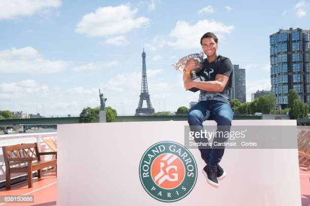 Rafael Nadal of Spain poses with the winner's trophy next to the Eiffel Tower and the Statue of Liberty Monument during a photocall to celebrate his...