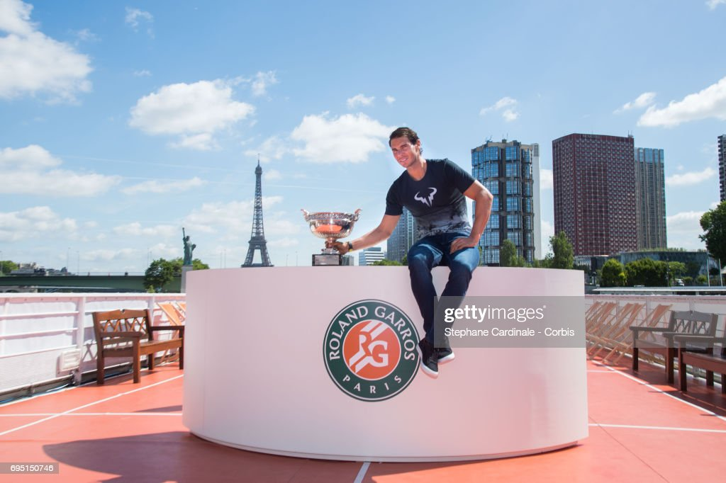 Rafael Nadal of Spain poses with the winner's trophy next to the Eiffel Tower and the Statue of Liberty Monument during a photocall to celebrate his record breaking 10th French Open title on the Seine River on June 12, 2017 in Paris, France.