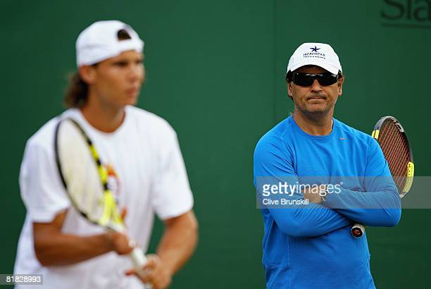 Rafael Nadal of Spain practices watched by coach and uncle Toni Nadal on day twelve of the Wimbledon Lawn Tennis Championships at the All England...