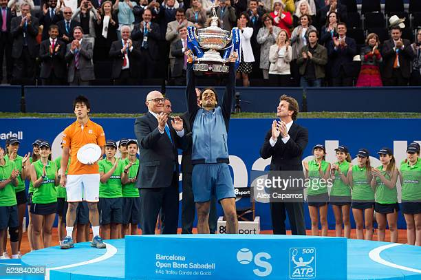 Rafael Nadal of Spain raises the trophy between President of Banc Sabadell Josep Oliu and Carlos Godo after defeating Kei Nishikori of Japan in the...