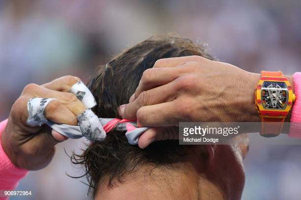 Rafael Nadal of Spain reties his headband between games in his third round match against Damir Dzumhur of Bosnia and Herzogovina on day five of the...
