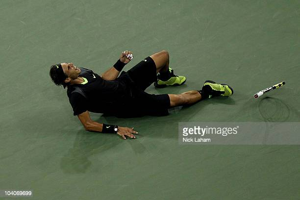 Rafael Nadal of Spain rolls on the ground in celebration of his win over Novak Djokovic of Serbia during their men's singles final on day fifteen of...
