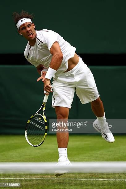 Rafael Nadal of Spain serves during his Gentlemen's Singles first round match against Thomaz Bellucci of Brazil on day two of the Wimbledon Lawn...