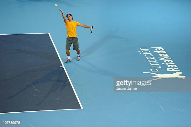 Rafael Nadal of Spain serves the ball to Roger Federer of Switzerland in a charity exhibition match at La Caja Magica on December 22 2010 in Madrid...