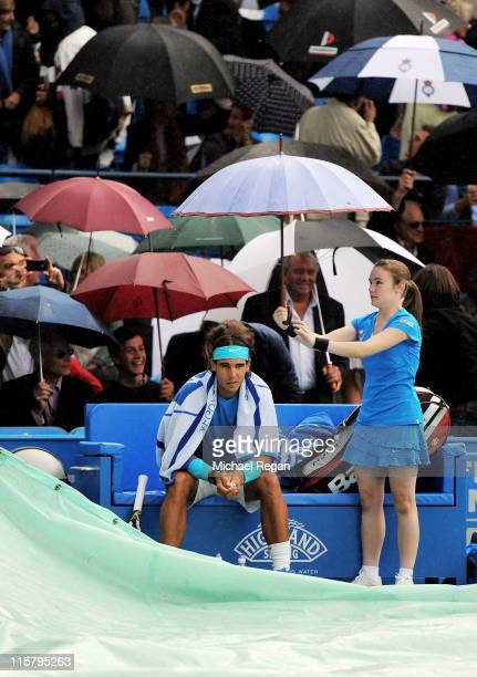 Rafael Nadal of Spain shelters under an umbrella on the sidelines as rain delays play during his Men's Singles quarter final match against JoWilfred...