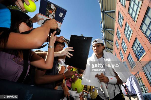 Rafael Nadal of Spain signs autographs following a practice session for the 2010 US Open at the USTA Billie Jean King National Tennis Center in...