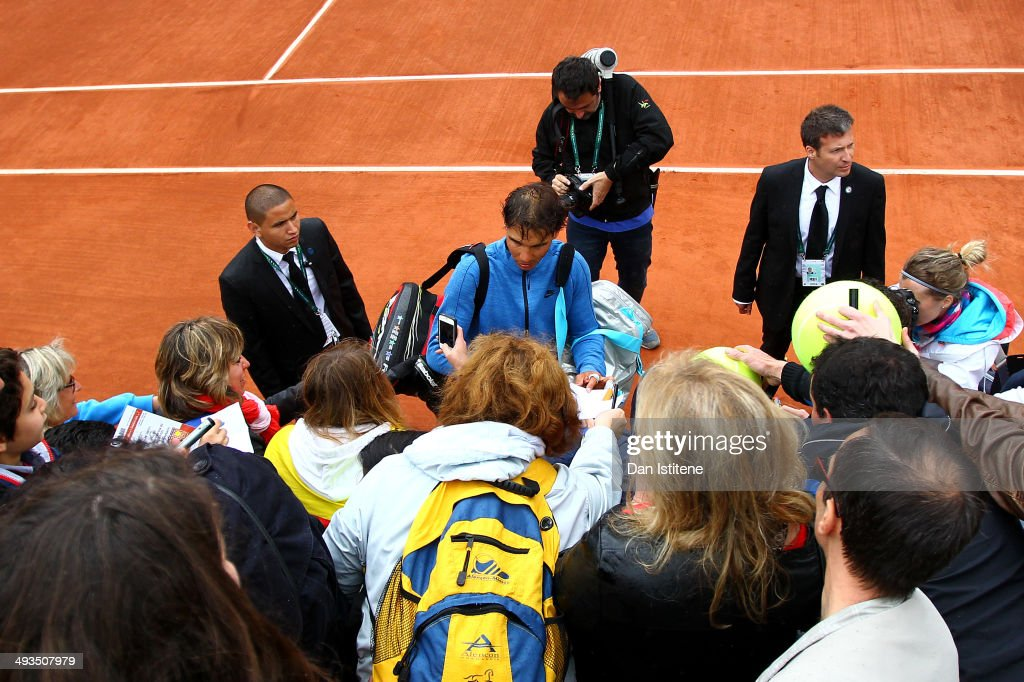 Rafael Nadal of Spain signs autographs for fans after a practice session ahead of the French Open at Roland Garros on May 24, 2014 in Paris, France.