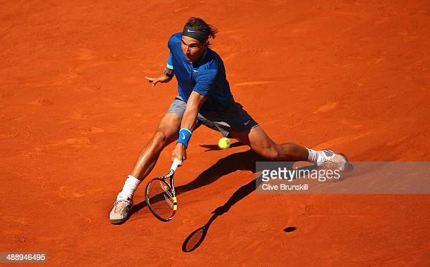 Rafael Nadal of Spain slides to reach a backhand against Tomas Berdych of the Czech Republic in their quarter final match during day seven of the...