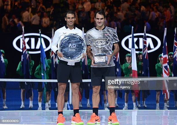 Rafael Nadal of Spain stands next to Roger Federer of Switzerland posing with the championship trophy after Australian Open 2017 men's final match...