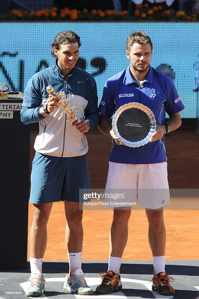 Rafael Nadal (L) of Spain stands with runner up Stanislas Wawrinka of Switzerland holding their trophies after Nadal won the final during the Mutua Madrid Open tennis tournament at La Caja Magica on May 12, 2013 in Madrid, Spain.