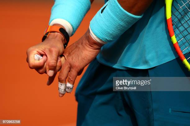 Rafael Nadal of Spain stretches off his fingers following an injury during the mens singles final against Dominic Thiem of Austria during day fifteen...