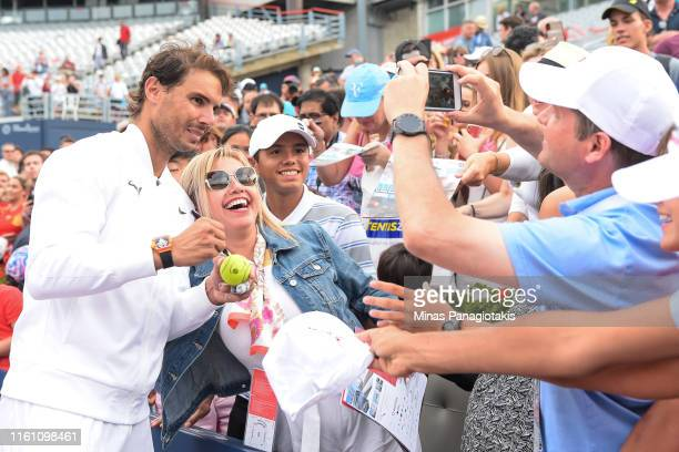 Rafael Nadal of Spain takes photos with fans after his win against Daniil Medvedev of Russia during the mens singles final on day 10 of the Rogers...