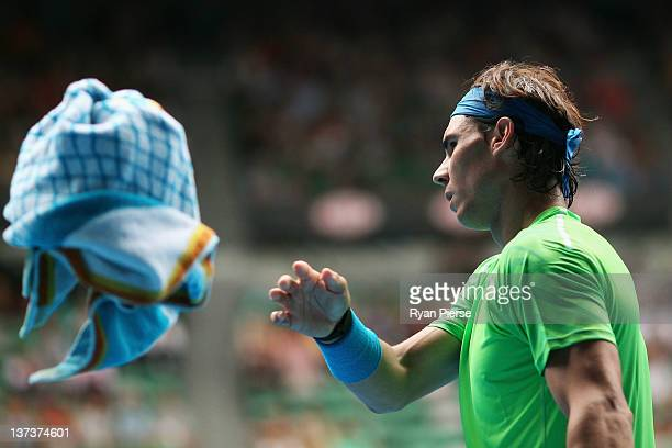 Rafael Nadal of Spain throws his towel to a ball kid in his third round match against Lukas Lacko of Slovakia during day five of the 2012 Australian...