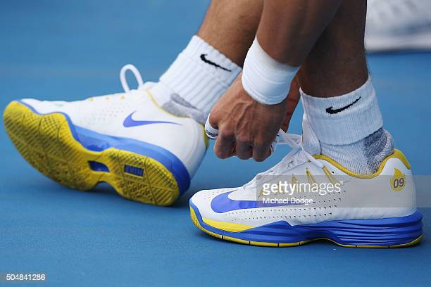 Rafael Nadal of Spain ties his shoes laces up after appearing to react in pain with his right ankle during a practice session ahead of the 2016...
