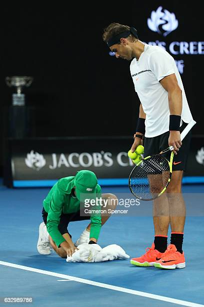 Rafael Nadal of Spain waits to serve as a ball kid picks up a moth in his headband in his Men's Final match against Roger Federer of Switzerland on...