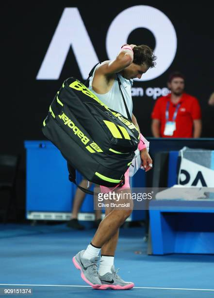 Rafael Nadal of Spain walks off the court after retiring injured during the fifth set in his quarterfinal match against Marin Cilic of Croatia on day...